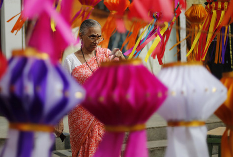A woman points a lantern on display at a roadside stall ahead of Diwali in Mumbai.