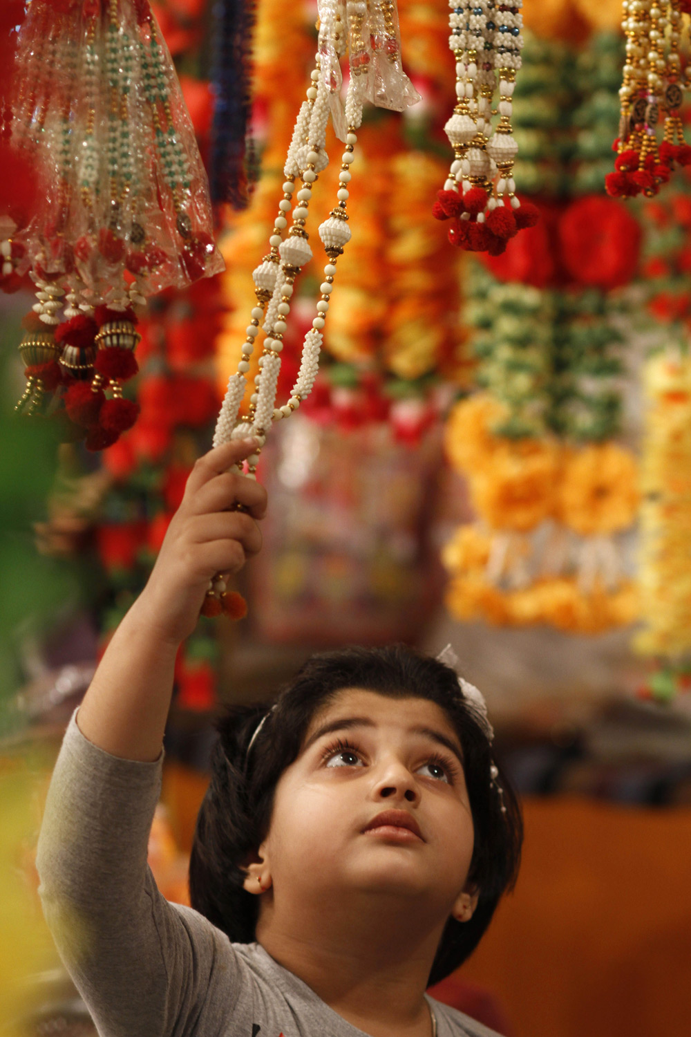 A girl touches an artificial garland on display at a shop ahead of Diwali in Allahabad.
