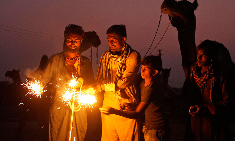 Camel herders, gathered for the annual cattle fair, play with firecrackers on the eve of Diwali in Pushkar.