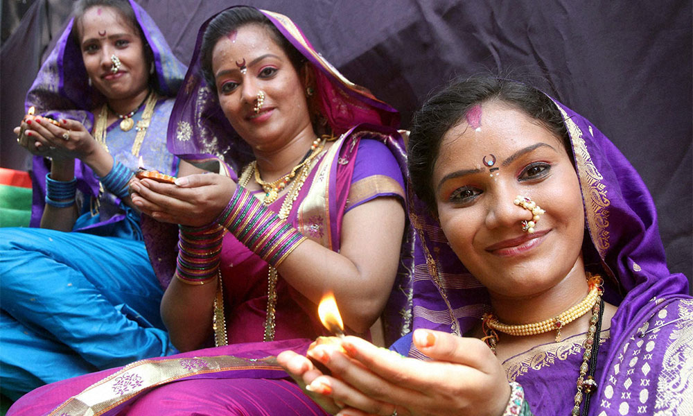 Artists pose with `diya` during an event to celebrate Diwali in Mumbai.