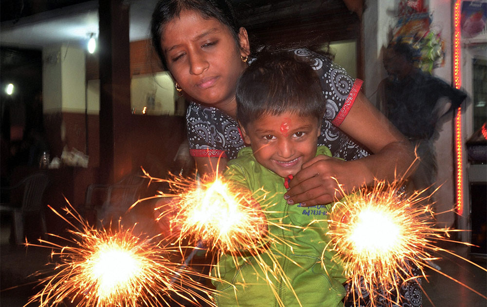 A child celebrating Diwali by lighting fire crackers in Bikaner.
