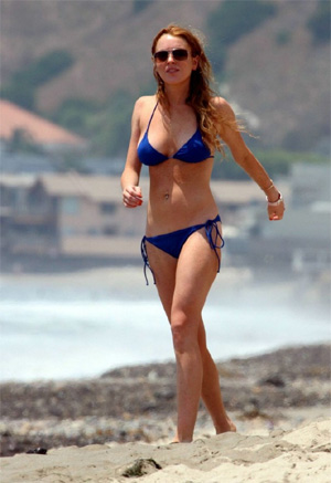 With her athletic body and Light blond hairtype without bra (cup size 34B) on the beach in bikini